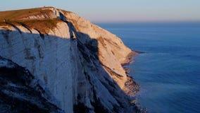 Ηλιοβασίλεμα πέρα από τους άσπρους απότομους βράχους στο Beachy κεφάλι στο Σάσσεξ Αγγλία απόθεμα βίντεο