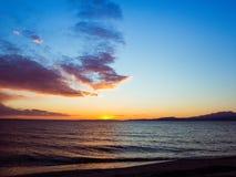 Ηλιοβασίλεμα πίσω από τα βουνά στον ορίζοντα, κενή παραλία στο πρώτο πλάνο στοκ εικόνες