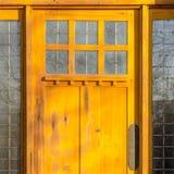 Ηλιοφώτιστη ξύλινη πόρτα με τα διακοσμητικά πλακάκια γυαλιού στοκ φωτογραφία με δικαίωμα ελεύθερης χρήσης