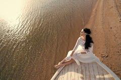 Ηλιόλουστη ημέρα γαμήλιων φορεμάτων νυφών η λατρευτή άσπρη κάθεται στη βάρκα ή το σκάφος Παραλία θάλασσας μήνα του μέλιτος Τα πρά στοκ φωτογραφία με δικαίωμα ελεύθερης χρήσης