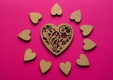 Ηλιόλουστη σύνθεση καρδιών από τη τοπ άποψη σχετικά με το ρόδινο υπόβαθρο Πόκερ-σχεδιασμός της ξύλινης καρδιάς στο κέντρο στοκ εικόνες