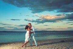 Ημερομηνία και ειδύλλιο ημερομηνία του προκλητικού νέου ζεύγους στο φίλημα λοβών στην παραλία ηλιοβασιλέματος το καλοκαίρι στοκ φωτογραφία με δικαίωμα ελεύθερης χρήσης