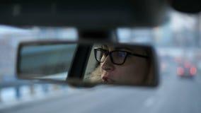 Η αντανάκλαση στον οπισθοσκόπο καθρέφτη των ματιών των γυναικών με τα γυαλιά 4K αργό MO απόθεμα βίντεο