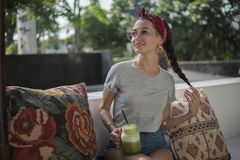 Η αρκετά πρότυπη τοποθέτηση στον πάγκο με τα μαξιλάρια στον υπαίθριο καφέ, σκοτεινός-μαλλιαρή ομορφιά κρατά την κοτσίδα τρίχας τη στοκ φωτογραφία με δικαίωμα ελεύθερης χρήσης