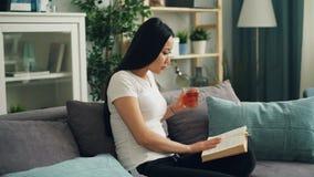 Η ασιατική νέα κυρία διαβάζει το βιβλίο και κρατά το φλυτζάνι του τσαγιού που γυρίζει τη σελίδα και που πίνει έπειτα τη συνεδρίασ φιλμ μικρού μήκους