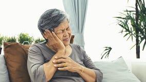 Η ασιατική ώριμη γυναίκα με την ηλικιωμένη γυναίκα με τον πονοκέφαλο παίρνει ένα χάπι, απόθεμα βίντεο