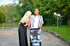 Η ασιατικοί μουσουλμανικοί μητέρα και ο πατέρας hijabi περπατούν μέσω του πάρκου με το γιο στον περιπατητή ενώ το mom του που φρο στοκ εικόνες με δικαίωμα ελεύθερης χρήσης