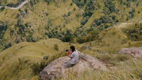 Η ατμοσφαιρική υψηλή γωνία πυροβοληθείσα, η νέα γυναίκα φωτογράφων παίρνουν τις φωτογραφίες του όμορφου πανοράματος θέας βουνού σ απόθεμα βίντεο