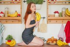 Η γοητεία του κοκκινομάλλους λεπτού κοριτσιού κάθεται στον πίνακα στο υπόβαθρο των ραφιών κουζινών με τα βάζα, γύρω από την πολύ  στοκ εικόνα με δικαίωμα ελεύθερης χρήσης