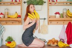 Η γοητεία του κοκκινομάλλους λεπτού κοριτσιού κάθεται στον πίνακα στο υπόβαθρο των ραφιών κουζινών με τα βάζα, γύρω από την πολύ  στοκ φωτογραφία με δικαίωμα ελεύθερης χρήσης