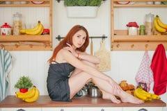Η γοητεία του κοκκινομάλλους λεπτού κοριτσιού κάθεται στον πίνακα στο υπόβαθρο των ραφιών κουζινών με τα βάζα, γύρω από την πολύ  στοκ φωτογραφίες με δικαίωμα ελεύθερης χρήσης