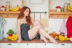Η γοητεία του κοκκινομάλλους λεπτού κοριτσιού κάθεται στον πίνακα στο υπόβαθρο των ραφιών κουζινών με τα βάζα, γύρω από την πολύ  στοκ εικόνες