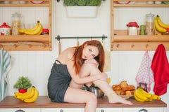 Η γοητεία του κοκκινομάλλους λεπτού κοριτσιού κάθεται στον πίνακα στο υπόβαθρο των ραφιών κουζινών με τα βάζα, γύρω από την πολύ  στοκ εικόνα