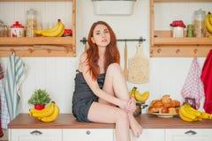 Η γοητεία του κοκκινομάλλους λεπτού κοριτσιού κάθεται στον πίνακα στο υπόβαθρο των ραφιών κουζινών με τα βάζα, γύρω από την πολύ  στοκ φωτογραφίες