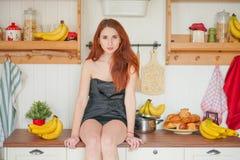 Η γοητεία του κοκκινομάλλους λεπτού κοριτσιού κάθεται στον πίνακα στο υπόβαθρο των ραφιών κουζινών με τα βάζα, γύρω από την πολύ  στοκ φωτογραφία