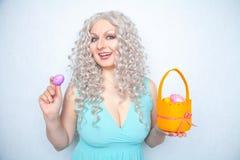 Η γοητεία του χαμογελώντας ξανθού εφήβου αντιπροσωπεύει σε ένα μπλε φόρεμα με ένα πορτοκαλί καλάθι με τα χρωματισμένα αυγά Πάσχα  στοκ φωτογραφία με δικαίωμα ελεύθερης χρήσης