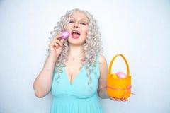 Η γοητεία του χαμογελώντας ξανθού εφήβου αντιπροσωπεύει σε ένα μπλε φόρεμα με ένα πορτοκαλί καλάθι με τα χρωματισμένα αυγά Πάσχα  στοκ φωτογραφία