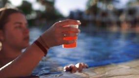 Η γυναίκα κολυμπά στην άκρη της πισίνας, παίρνει το φρέσκο χυμό, τον πίνει και κολυμπά μακριά, ηλιόλουστη ημέρα στην πισίνα απόθεμα βίντεο