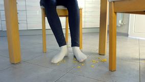 Η γυναίκα μαζεύει με τη τσουγκράνα crumbs ποδιών του στο πλαίσιο του πίνακα Περισσεύματα στο πάτωμα κουζινών, βρώμικο πάτωμα κουζ απόθεμα βίντεο