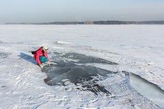 Η γυναίκα σε ένα κόκκινο σακάκι εξετάζει το διαφανή πάγο στον ποταμό, δεξαμενή Ob, Σιβηρία, Ρωσία στοκ φωτογραφία με δικαίωμα ελεύθερης χρήσης