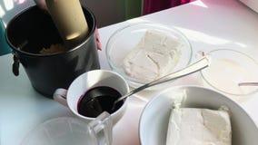Η γυναίκα σφραγίζει τη βάση για cheesecake σε μια μεταλλική μορφή με μια ξύλινη κυλώντας καρφίτσα απόθεμα βίντεο