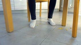 Η γυναίκα τρώει στον πίνακα και θρυμματίζει τις νιφάδες καλαμποκιού στο πάτωμα Πόδια και πάτωμα, μπροστινή άποψη απόθεμα βίντεο