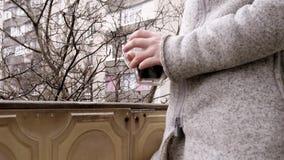 Η γυναίκα πίνει τον καφέ στο μπαλκόνι