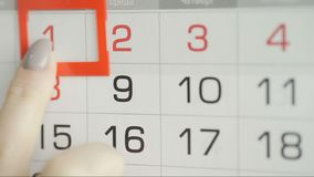 Η γυναίκα παραδίδει την ημερομηνία αλλαγών γραφείων στο ημερολόγιο τοίχων Αλλαγές 1 έως 2 φιλμ μικρού μήκους
