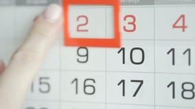 Η γυναίκα παραδίδει την ημερομηνία αλλαγών γραφείων στο ημερολόγιο τοίχων Αλλαγές 2 έως 3 φιλμ μικρού μήκους