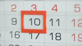 Η γυναίκα παραδίδει την ημερομηνία αλλαγών γραφείων στο ημερολόγιο τοίχων Αλλαγές 9 έως 10 απόθεμα βίντεο
