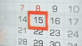 Η γυναίκα παραδίδει την ημερομηνία αλλαγών γραφείων στο ημερολόγιο τοίχων Αλλαγές 14 έως 15 απόθεμα βίντεο