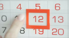 Η γυναίκα παραδίδει την ημερομηνία αλλαγών γραφείων στο ημερολόγιο τοίχων Αλλαγές 11 έως 12 απόθεμα βίντεο