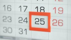 Η γυναίκα παραδίδει την ημερομηνία αλλαγών γραφείων στο ημερολόγιο τοίχων Αλλαγές 24 έως 25 απόθεμα βίντεο