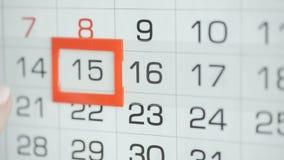 Η γυναίκα παραδίδει την ημερομηνία αλλαγών γραφείων στο ημερολόγιο τοίχων Αλλαγές 15 έως 16 απόθεμα βίντεο