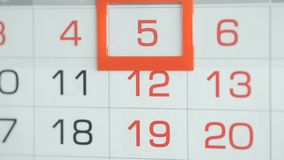Η γυναίκα παραδίδει την ημερομηνία αλλαγών γραφείων στο ημερολόγιο τοίχων Αλλαγές 4 έως 5 απόθεμα βίντεο