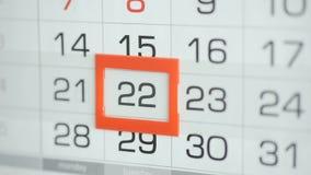 Η γυναίκα παραδίδει την ημερομηνία αλλαγών γραφείων στο ημερολόγιο τοίχων Αλλαγές 21 έως 22 απόθεμα βίντεο