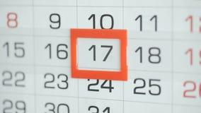 Η γυναίκα παραδίδει την ημερομηνία αλλαγών γραφείων στο ημερολόγιο τοίχων Αλλαγές 16 έως 17 απόθεμα βίντεο