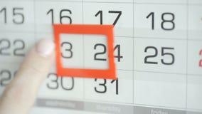 Η γυναίκα παραδίδει την ημερομηνία αλλαγών γραφείων στο ημερολόγιο τοίχων Αλλαγές 23 έως 24 απόθεμα βίντεο
