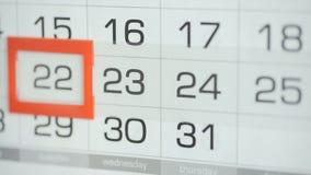 Η γυναίκα παραδίδει την ημερομηνία αλλαγών γραφείων στο ημερολόγιο τοίχων Αλλαγές 22 έως 23 απόθεμα βίντεο