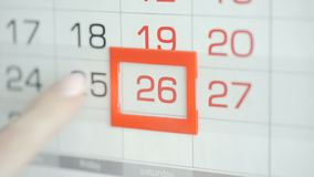 Η γυναίκα παραδίδει την ημερομηνία αλλαγών γραφείων στο ημερολόγιο τοίχων Αλλαγές 25 έως 26 απόθεμα βίντεο