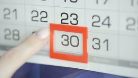 Η γυναίκα παραδίδει την ημερομηνία αλλαγών γραφείων στο ημερολόγιο τοίχων Αλλαγές 29 έως 30 απόθεμα βίντεο