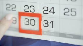 Η γυναίκα παραδίδει την ημερομηνία αλλαγών γραφείων στο ημερολόγιο τοίχων Αλλαγές 30 έως 31 απόθεμα βίντεο