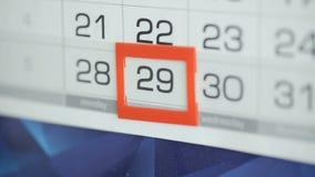 Η γυναίκα παραδίδει την ημερομηνία αλλαγών γραφείων στο ημερολόγιο τοίχων Αλλαγές 28 έως 29 απόθεμα βίντεο
