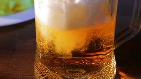 Η ελαφριά μπύρα χύνεται σε μια κούπα γυαλιού φιλμ μικρού μήκους