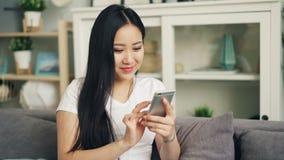 Η ελκυστική ασιατική γυναίκα στην άσπρη μπλούζα χρησιμοποιεί το smartphone σχετικά με την οθόνη που χαμογελά και που γελά ελέγχον απόθεμα βίντεο