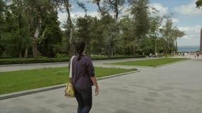 Η ελκυστική γυναίκα Yound με το ελκυστικό hairset περπατά προς το μνημείο κοντά στη θάλασσα r απόθεμα βίντεο