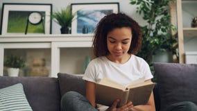 Η ελκυστική νέα γυναίκα αφροαμερικάνων διαβάζει το βιβλίο απολαμβάνοντας τη σύγχρονη συνεδρίαση λογοτεχνίας στον καναπέ στο σπίτι φιλμ μικρού μήκους