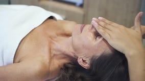 Η ενήλικη γυναίκα βρίσκεται στον πίνακα μασάζ και παίρνει επαγγελματική, ιατρικός, ενεργειακή διαδικασία φιλμ μικρού μήκους