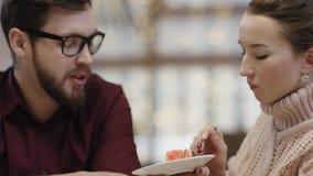 Η ενήλικη γυναίκα ταΐζει τον άνδρα της με ένα κέικ και το τρώει από μόνη της σε έναν καφέ απόθεμα βίντεο