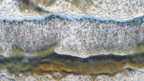 Η εναέρια άποψη της παραλίας της Ισπανίας τα κύματα έρχεται στην ακτή και διαμορφώνει τον αφρό και τις φυσαλίδες από την ακτή το  φιλμ μικρού μήκους